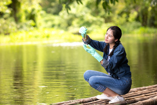Asian student biology taking and testing sample of natural river water.  Experts science women keep water for research analysis in the laboratory.  Environmental pollution Concept