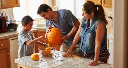 hispanic american family carving pumpkin into jack o lantern at home
