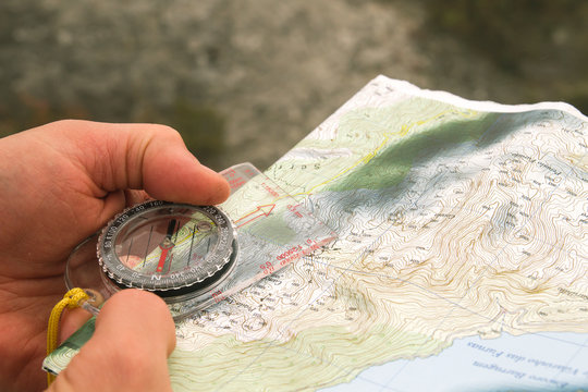 Explorer using a compass and topographic map