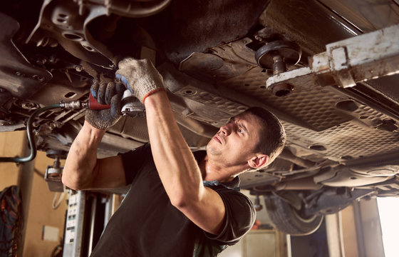 Repairman fixing car in garage. Experienced specialist car mechanic standing under lifted car during repair and maintenance process in repair station. Workshop for automobile checking up and repairing