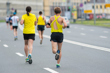 Runners on the city road. Sport competitions. Fitness and healthy lifestyle concept