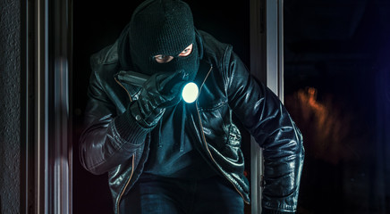 Masked burglar with torch and crowbar breaking and entering into a house - shot with dramatic motion