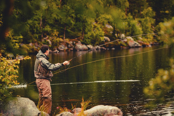 Photo sur Toile Peche Coil of fly fishing rope, man hands holding rod
