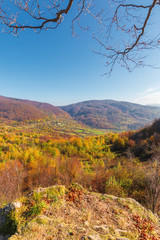 autumn scenery in mountains on a sunny day. view from a high vantage point in to the distant valley. trees in colorful foliage. rail station and viaduct in the distance. abandoned place