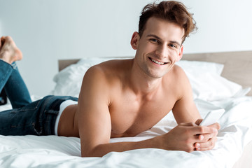 happy man in jeans using smartphone and lying in bedroom