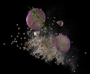 Red onion, garlic,rosemary and pepper splash or explosion flying in the air isolated on black background