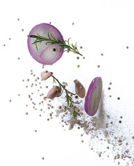 Red onion, garlic,rosemary and pepper splash or explosion flying in the air isolated on white background