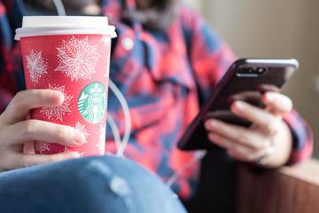 Bangkok ,Thailand November 27 : woman hold starbucks hot beverage cup in Christmas theme using smartphone