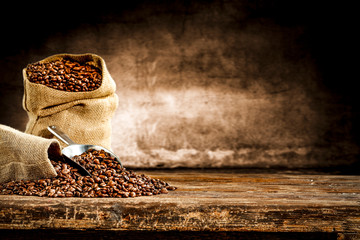 Fotobehang Koffiebonen Fresh old sack of coffee grains and brown old wall background