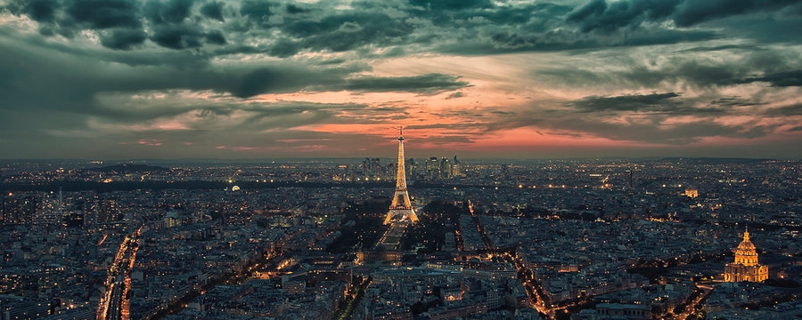 Paris city in the evening with the Eiffel tower and La Defense business district illuminated