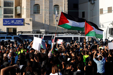 People hold Palestinian flags and placards in front of a police station as they protest against what Israeli Arabs citizens claim is Israeli police inaction to the violent crimes in their towns, in Majd al-Krum, northern Israel