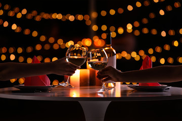 Tuinposter Wijn Young couple with glasses of wine having romantic candlelight dinner at table, closeup