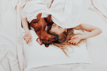 Beautiful girl lying relax in bed with her beloved dog. morning prodding in a warm comfortable bed. cute woman and her dog are sleeping in the bed covered with a blanket. - Image