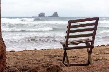 Old wooden beach chair facing the ocean, on an overcast and gloomy morning, Ayampe, Manabi, Ecuador