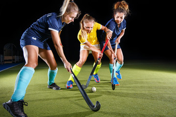 Field hockey female players struggle for the ball