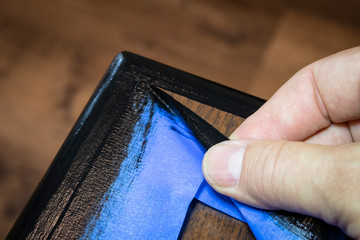 Hand removing blue painter's tape from edge of refinished furniture paint job. Wall mural