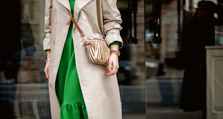 Fashionable bag close-up in female hands.Girl walks in the city outdoors. Stylish modern and feminine image, style. Girl in a beige cloak or coat and a green dress with a bag on his shoulder.