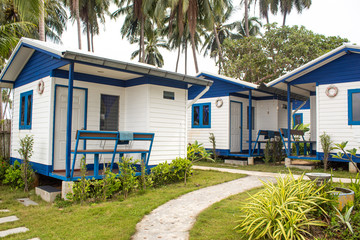 Blue and white holiday houses in green paradise landscape