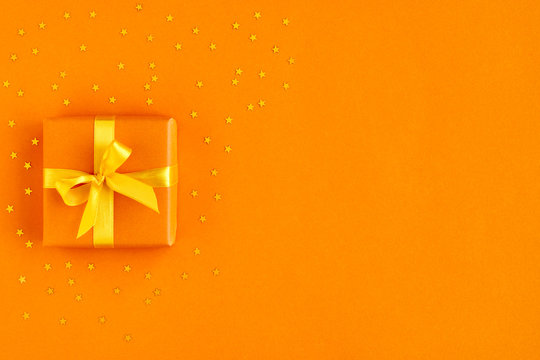 Gift box with ribbon and bow on orange background with gold stars . Top view and space for text.