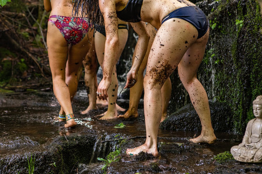 Diverse people enjoy spiritual gathering Barefooted women in lingerie wash and bathe in natural mud at a rock pool during a rural retreat celebrating native cultures and beliefs.