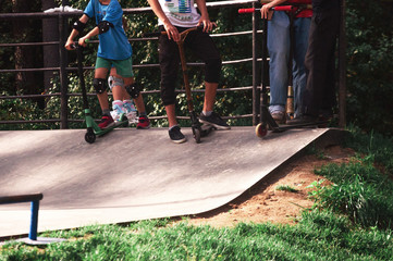 Several teenagers at a skate park on a sunny day. Prepare for the descent, have fun and communicate.