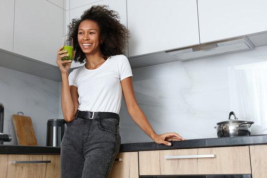 Woman drinking green detox juice, smoothie drink in kitchen