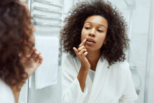 Lips skin care. Woman applying lip balm in bathroom portrait