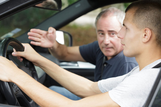 driving instructor gesturing to young learner driver