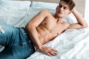 sexy and shirtless man in blue jeans lying on bed