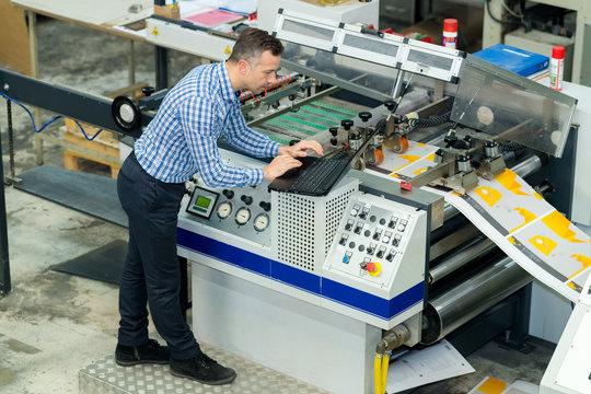 manworking on printing machine in print factory