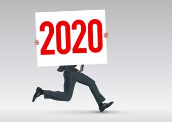 Pour présenter la stratégie de l'entreprise, un homme en costume cravate cours en portant une pancarte blanche sur laquelle est écrit l'année 2020