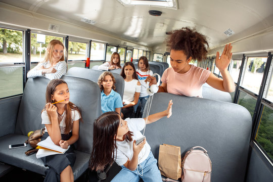 Children going to school by bus sitting girl taking classmate headphones bully aggressive