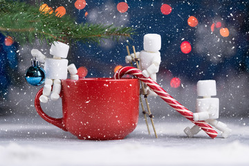 Three funny marshmallow men decorate christmas tree by candy cane and christmas tree ball on snowing background