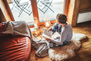 Boy reading book on the floor on sheepskin in cozy home atmosphere. Peaceful moments of cozy home concept image.
