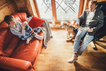 Father, son and his beagle dog spending holiday time in cozy country house. Dad reading a book, boy sitting and listening, dog looking in window. Winter family vacation