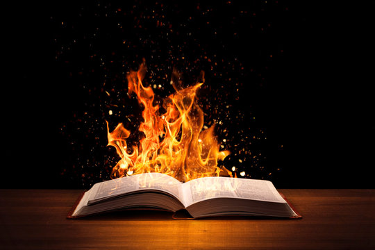 Holy Bible on fire on a wooded desk