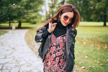 Smiling female dressed boho fashion style colorful long dress with black leather biker jacket with brown leather flap bag having a autumn park walking.