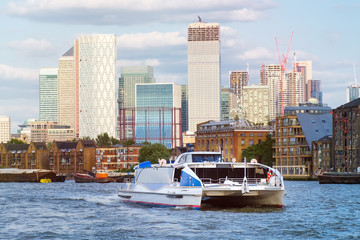 Catamaran on the river Thames in London with Canary Wharf on the