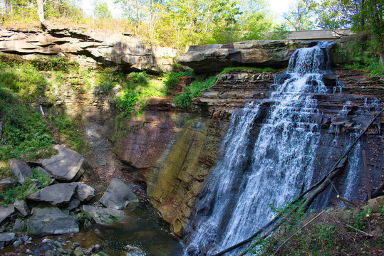 Brandywine Falls at Cuyahoga Valley National Park. Blue water rushing over colorful rocks on a sunny day. Isolated in forest.