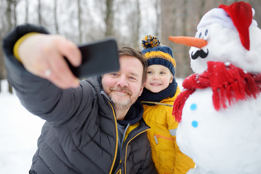Little boy and his father taking selfie on background of snowman in snowy park. Active outdoors leisure with children in winter.