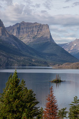 Wall Mural - Beautiful View of a Glacier Lake with American Rocky Mountain Landscape in the background during a Cloudy Summer Morning. Taken in Glacier National Park, Montana, United States.