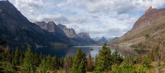 Wall Mural - Beautiful Panoramic View of a Glacier Lake with American Rocky Mountain Landscape in the background during a Cloudy Summer Morning. Taken in Glacier National Park, Montana, United States.