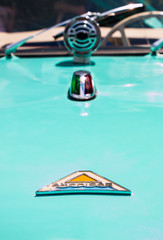 The emblem on the hood of a blue Amphicar, an amphibious automobile.