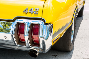 The right rear end of a yellow Oldsmobile 442 with the emblem showing.