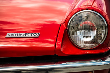 The front headlamp and emblem for a red Triumph Spitfire 1500 automobile.