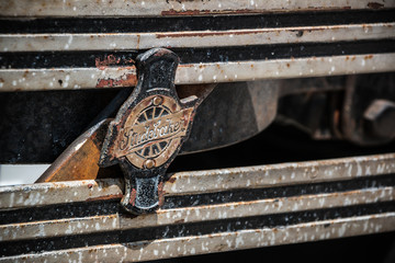 Old, rusted emblem on the front bumper of a classic Studebaker automobile.