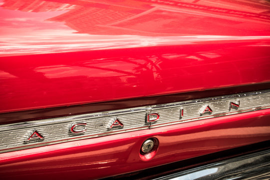 Nameplate from a classic red Acadian automobile, made by General Motors for Canadian customers.