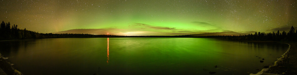 Bright green and orange Aurora (Northern Lights) , stars and clouds reflecting in a calm lake.
