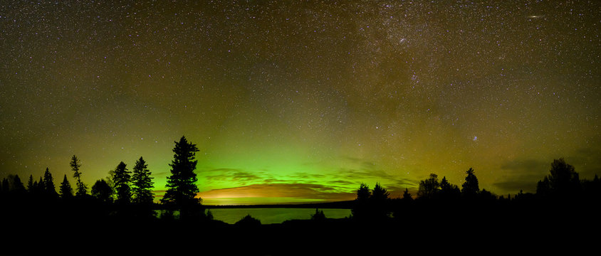 Bright green and orange Aurora (Northern Lights) , stars and clouds reflecting in a calm lake.  Includes Andromeda galaxy.