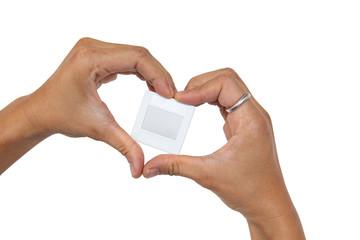 Hands in heart form love slide film mount frame on white background.